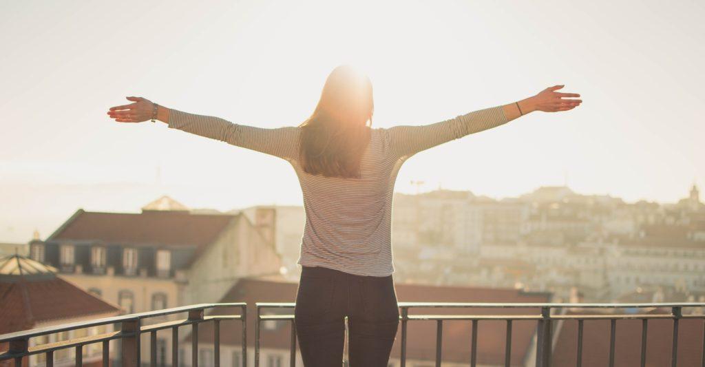 Mulher de braços abertos na varanda com luz do sol ao fundo